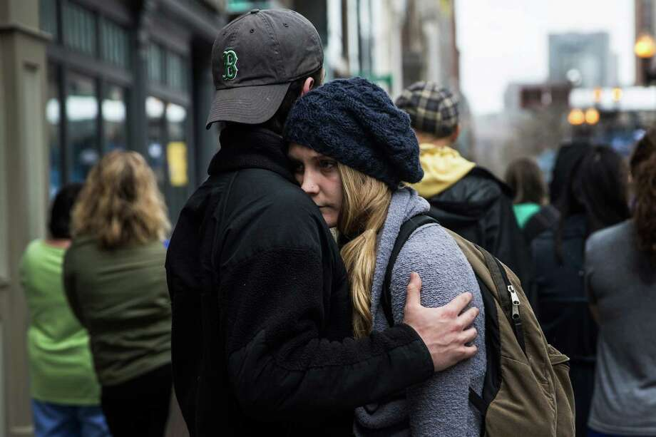 BOSTON, MA - APRIL 15:  Tom Duggan hugs Sarah Rogo, who said they were both present last year at the marathon, while a billboard television screen broadcasts the ceremony commemorating the one year anniversary of the 2013 Boston Marathon Bombing , on April 15, 2014 in Boston, Massachusetts. Last year, two pressure cooker bombs killed three and injured an estimated 264 others during the Boston marathon, on April 15, 2013. Neary says she was standing near the site of the bombing before it went off.  (Photo by Andrew Burton/Getty Images) ORG XMIT: 485055841 Photo: Andrew Burton, Getty / 2014 Getty Images