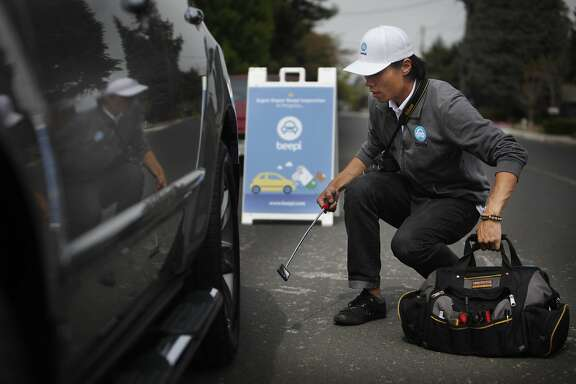 Dae Yu, Beepi lead inspector, uses an extendable mirror while inspecting Kimberly Walker's Acura MDX on Friday, April 11, 2014,  in Mountain View, Calif.
