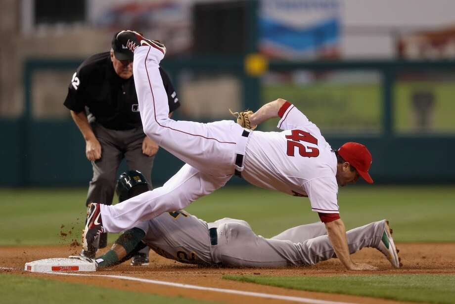 Third baseman David Freese of the Los Angeles Angels of Anaheim falls over Yoenis Cespedes of the Oakland Athletics after tagging him out as he was attempting to advance in the second inning at Angel Stadium of Anaheim on April 15, 2014 in Anaheim, California. Photo: Jeff Gross, Getty Images