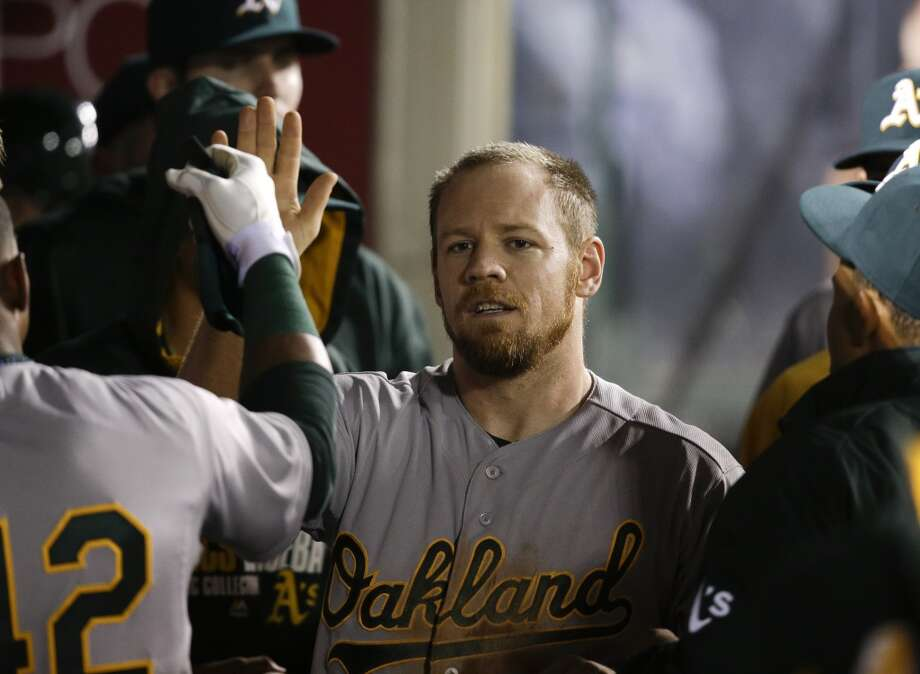 Oakland Athletics' Brandon Moss, center, is greeted by teammates after he scored on a single hit by Derek Norris during the eighth inning of a baseball game against the Los Angeles Angels on Tuesday, April 15, 2014, in Anaheim, Calif. Photo: Jae C. Hong, Associated Press