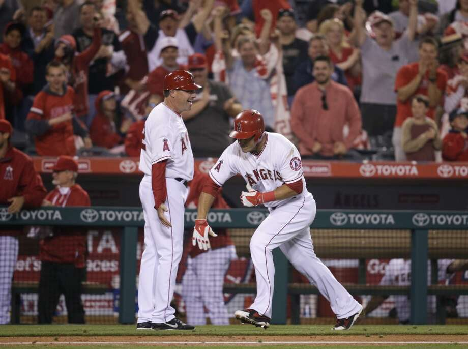 Los Angeles Angels' Mike Trout, right, celebrates his game-tying two-run home run with third base coach Gary DiSarcina during the ninth inning of a baseball game against the Oakland Athletics on Tuesday, April 15, 2014, in Anaheim, Calif. Photo: Jae C. Hong, Associated Press