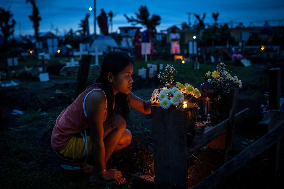 "A woman tends to the gravesite of a loved one at the makeshift mass grave site at San Joaquin Parish on April 16, 2014 in Tacloban, Leyte, Philippines. People continue to rebuild their lives five months after Typhoon Haiyan struck the coast  on November 8, 2013, leaving more than 6000 dead and many more homeless. Although many businesses and services are functioning, electricity and housing continue to be the main issues, with many residents still living in temporary housing conditions due to ""No Build"" areas preventing them from rebuilding their homes. This week marks Holy Week across the Philippines and will see many people attend religious activities. Photo: Chris McGrath, Getty Images"