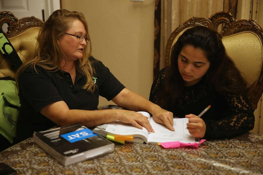 Carol McMullen-Pettit, a Princeton Review tutor, helps 11th-grader Suzane Nazir prepare for the SAT last month in Pembroke Pines, Fla. The exam was taken by 1.7 million students in 2013. Photo: Joe Raedle, Getty Images