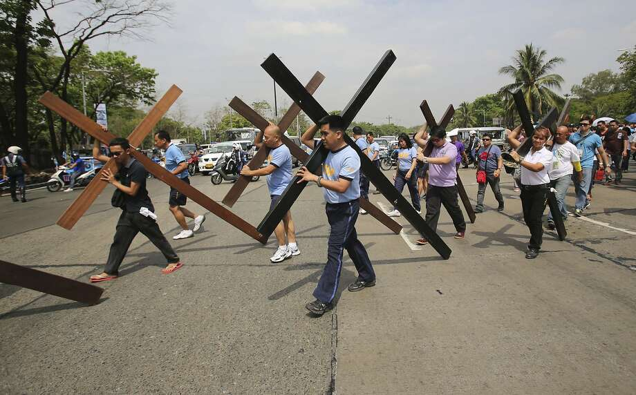 Filipino policemen and government workers carry wooden crosses to reenact the suffering of Jesus Christ as part of their observation of lent along a road in suburban Quezon city, north of Manila, Philippines during Holy Wednesday, April 16, 2014. Devotees practice different religious rites to atone for their sins and pray for more blessings during the Holy Week in this predominantly Roman Catholic country. Photo: Aaron Favila, Associated Press