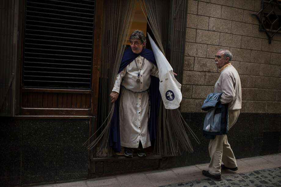 "A penitent, left, leaves a bar prior to take part in the procession of the ""Silencio del Santisimo Cristo del Rebate"" brotherhood, during Holy Week in Tarazona, northern Spain, Tuesday, April 15, 2014. Hundreds of processions take place throughout Spain during the Easter Holy Week. Photo: Alvaro Barrientos, Associated Press"