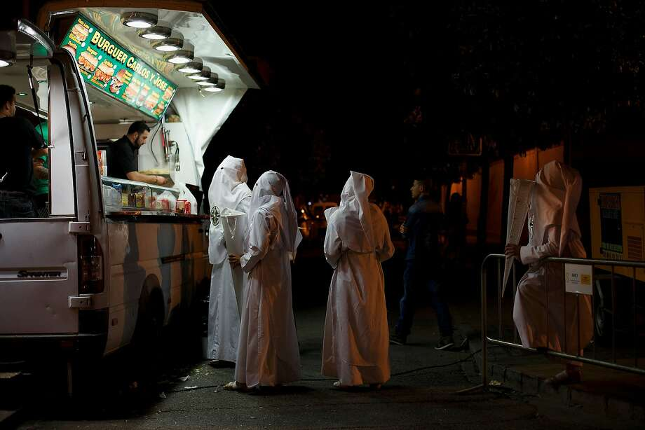 Penitents from 'San Gonzalo' brotherhood buy food at a mobile street food van after a 12 hour procession outside their church in the early hours on April 15, 2014 in Seville, Spain. Easter week is traditionally celebrated with processions in most Spanish towns. Photo: Pablo Blazquez Dominguez, Getty Images