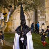 "Children play in the background as a penitent watches a march from ""Jesus en su Tercera Caída"" brotherhood during a procession in Zamora, Spain, Monday, April 14, 2014. Hundreds of processions take place throughout Spain during the Easter Holy Week."