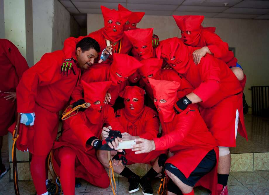 "Masked faithfuls dressed as devils, popularly known as ""Talciguin"", take a selfie during the celebration of an ancient local tradition that marks the start of Holy Week, on April 14, 2014 in Texistepeque, some 84 km west of San Salvador, El Salvador. Talciguines lash Catholic faithfuls to cleanse their sins. Photo: Jose Cabezas, AFP/Getty Images"