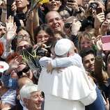 Pope Francis is hugged by a child at the end of the Palm Sunday Mass in St. Peter's square at the Vatican, Sunday, April 13, 2014. Tens of thousands of Romans, tourists and pilgrims have joined Pope Francis in a solemn Palm Sunday service in St. Peter's Square. Palm Sunday begins Holy Week, which culminates next Sunday on Easter. Francis used a pastoral staff made of wood carved by Italian prison inmates, who donated it to him. The pope is determined to put people on the margins of life at the center of the Roman Catholic church's attention.