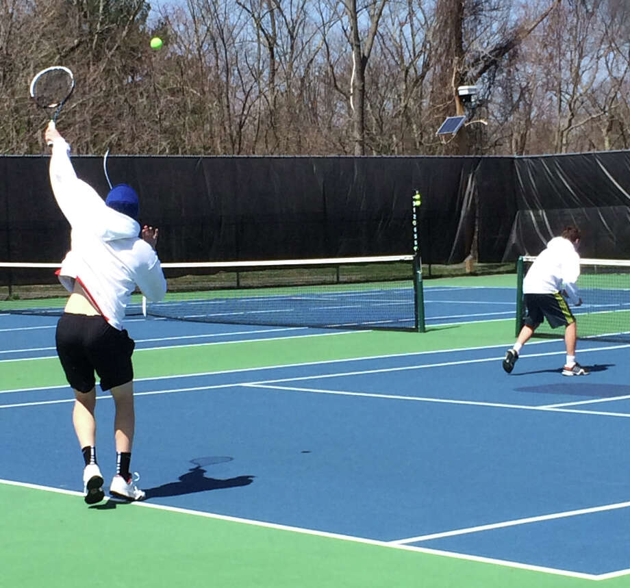 New Canaan's Andrew Penchuk serves in the No. 1 doubles match against Ridgefield alongside partner Tommy Knortz at New Canaan High School on Wednesday, April 16. Photo: Andrew Callahan / New Canaan News
