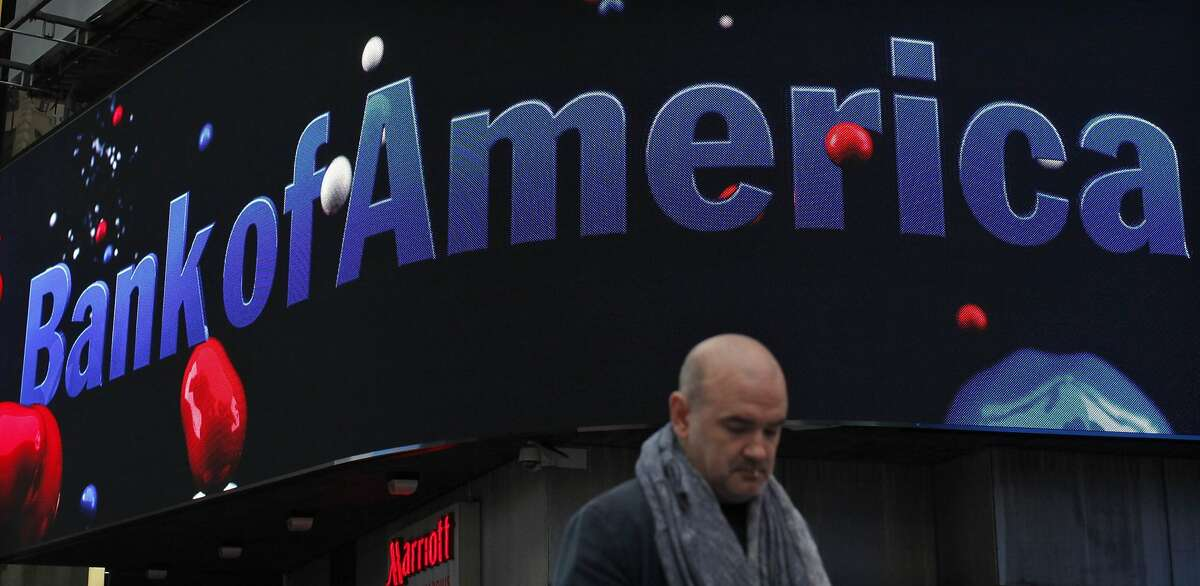 A man walks next to a Bank of America branch in New York in this file photo taken October 24, 2012. Bank of America Corp posted a first-quarter loss on Wednesday as it set aside an extra $6 billion to cover litigation expenses, a figure that far exceeded the legal settlements the No. 2 U.S. bank has announced recently. REUTERS/Eduardo Munoz/Files (UNITED STATES - Tags: BUSINESS)