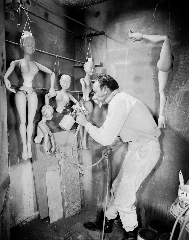 A man air brushes puppets in preparation for Sid and Marty Krofft's 'Poupees de Paris', a puppet extravaganza at New York's World Fair in which a cast of 240 puppet caricatures of famous entertainers, sing, dance and act out humorous skits. Photo: Keystone Features, Getty Images / Hulton Archive