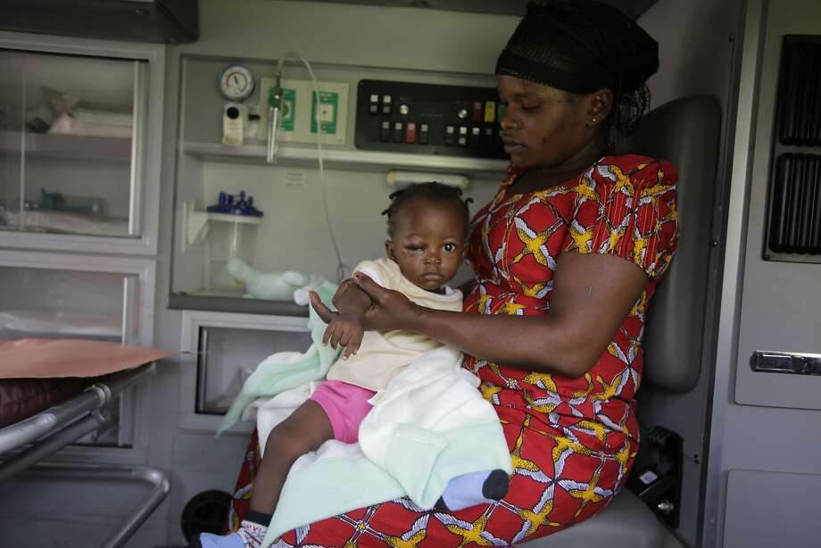 A 10-month-old baby is brought to a hospital by her aunt after an Abuja bus station bombing. Photo: Sunday Alamba, Associated Press