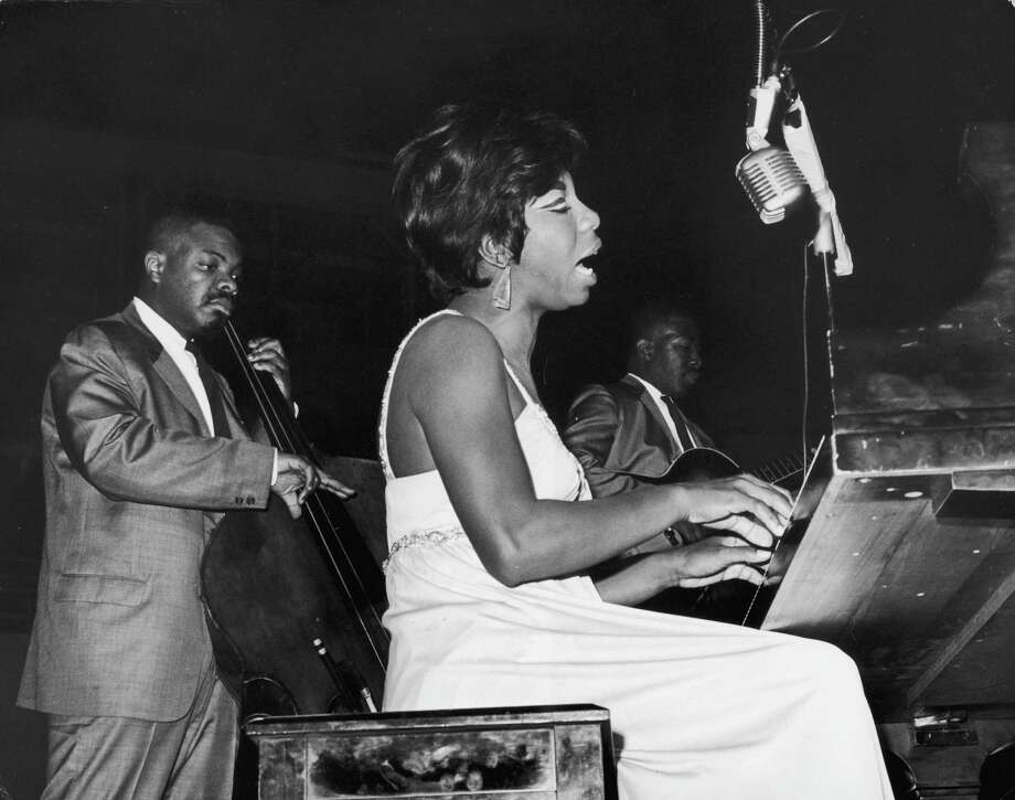 American pianist and vocalist Nina Simone sings while playing piano at the World's Fair, Singers' Bowl, Queens, New York.  A bassist and a guitarist play in the background. Photo: Hulton Archive, Getty Images / Archive Photos