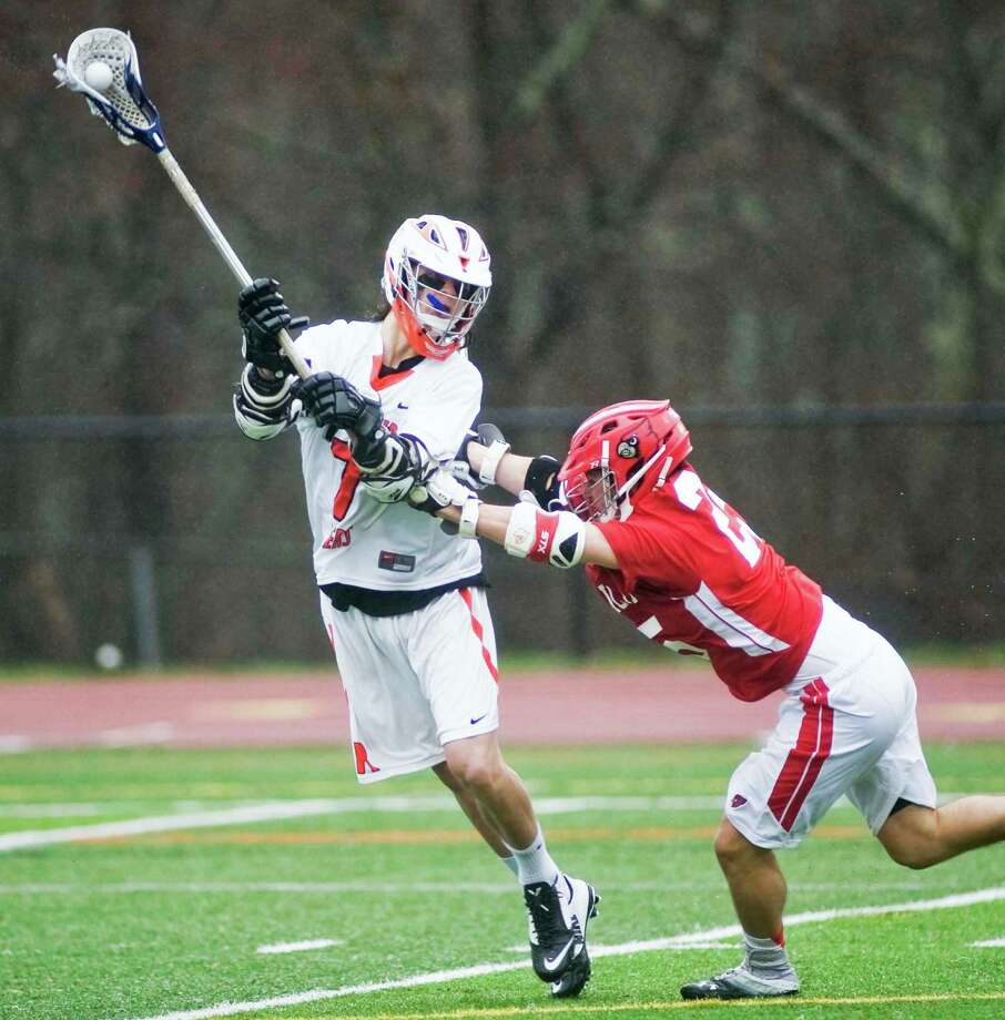 Ridgefield High School's Simon Mathias takes a hit by Greenwich High School's Nick Schepis during a game at Ridgefield. Tuesday, April 15, 2014 Photo: Scott Mullin / The News-Times Freelance