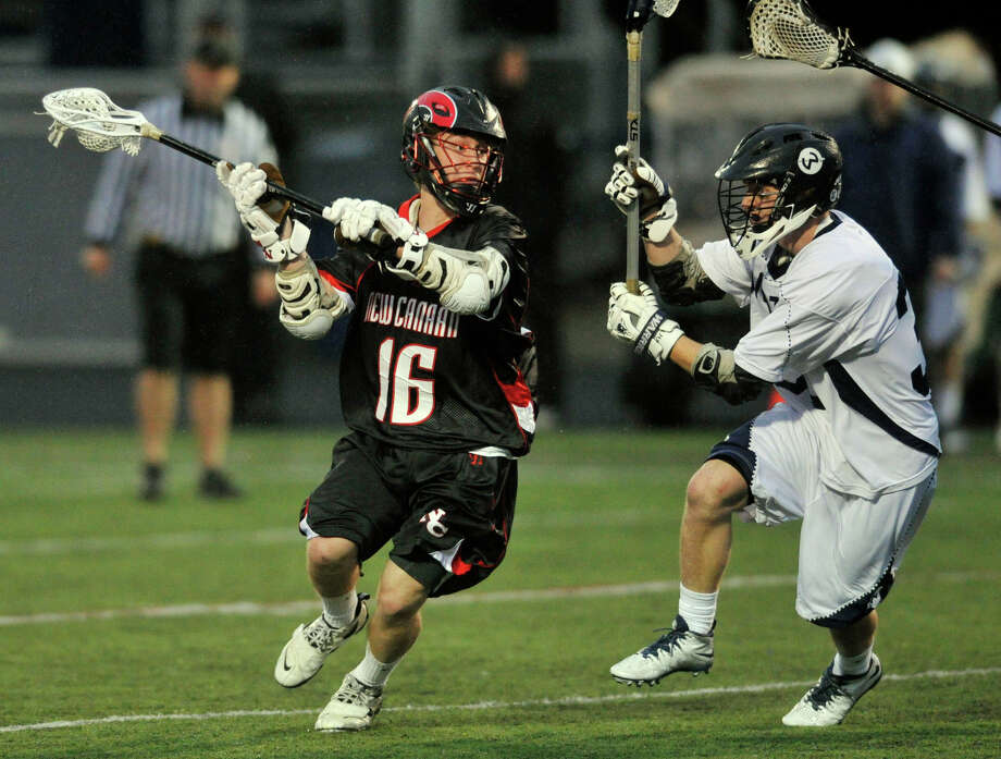 New Canaan's Henry Stanton fires a shot while under pressur from Wilton's Joseph Collias during their lacrosse game at Wilton High School in Wilton, Conn., on Tuesday, April 15, 2014. Photo: Jason Rearick / Stamford Advocate