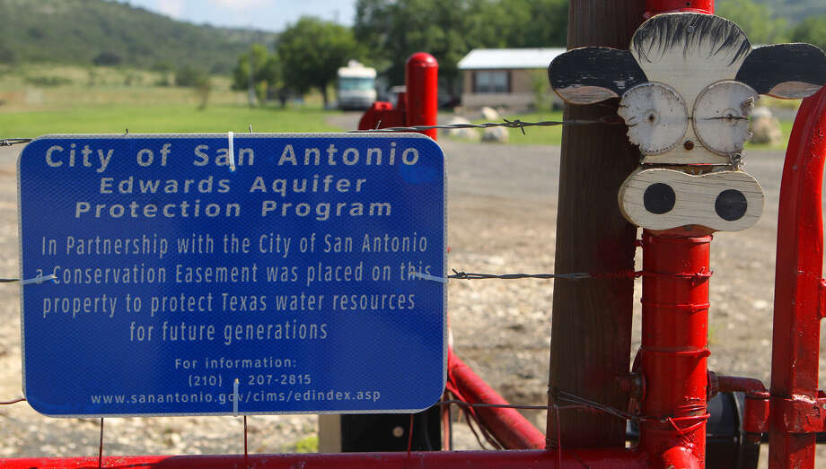 A sign by the gate of the Marneldo Ranch near Sabinal lets visitors know that the ranch owners are taking part in the city of San Antonio Edwards Aquifer Protection Program. San Antonio should continue the program. Photo: Express-News File Photo / SAN ANTONIO EXPRESS-NEWS (Photo can be sold to the public)