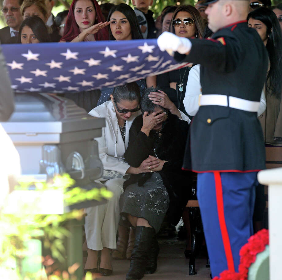 The coffin flag is removed and supporters comfort the widow Pauline Ayala as Tony Ayala Sr. is remembered at funeral services at Palm Heights Mortuary and Ft. Sam Houston National Cemetery on April 16, 2014. Photo: TOM REEL