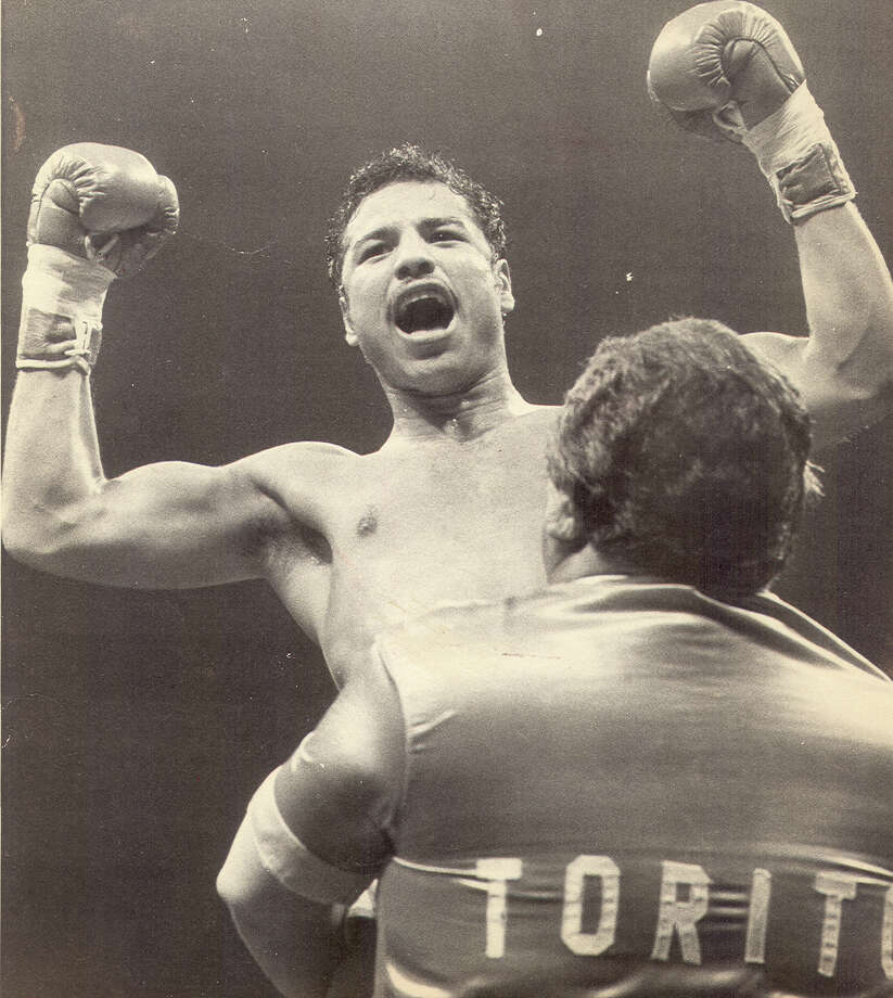 Tony Ayala Jr. is lifted up by his father Tony Ayala Sr. after a 1982 fight. Photo: Express-News File Photo / San Antonio Express-News