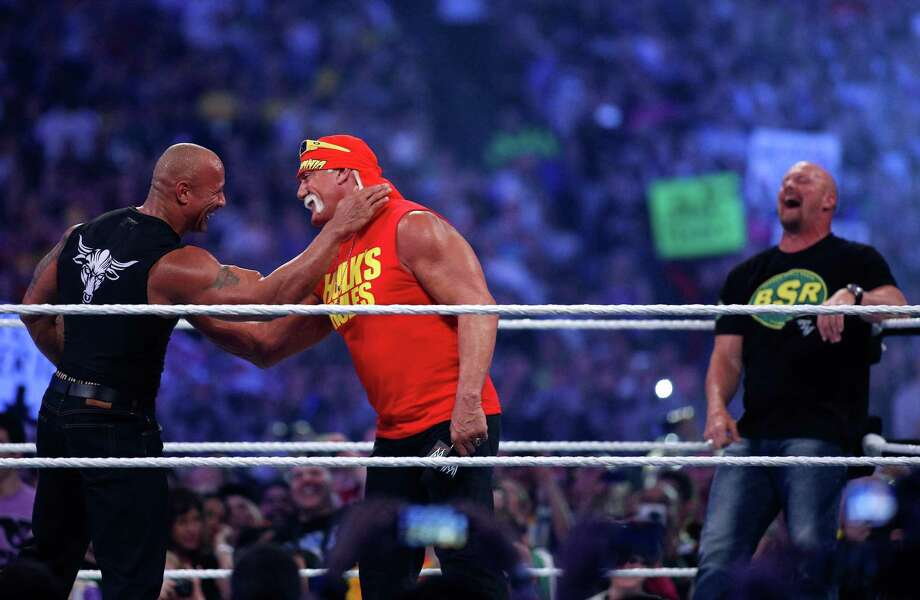Dwayne Johnson aka The Rock, left, embraces Hulk Hogan, center during Wrestlemania XXX at the Mercedes-Benz Super Dome in New Orleans on Sunday, April 6. (Jonathan Bachman/AP Images for WWE) Photo: Contributed Photo, Associated Press / Stamford Advocate Contributed