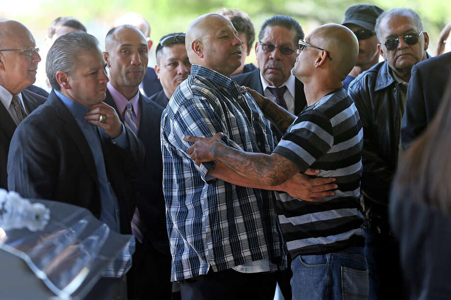 Tony Ayala, Jr. is consoled by supporters including  George Moreno who's family trained with the former champion as Tony Ayala Sr. is remembered at funeral services at Palm Heights Mortuary and Ft. Sam Houston National Cemetery on April 16, 2014. Photo: TOM REEL