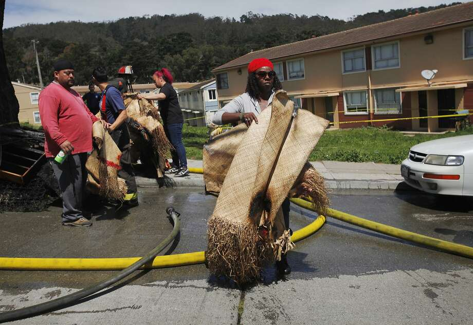 Neighbors help a victim of the fire remove traditional Samoan prayer mats after a blaze in April that killed two people at the Sunnydale public housing complex in San Francisco. Photo: Leah Millis, San Francisco Chronicle