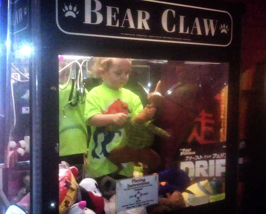 In this April 14, 2014 photo provided by Rachelle Hildreth, a 3-year-old boy plays with stuffed toys inside a claw crane game machine at a bowling alley in Lincoln, Neb. Police say a 24-year-old woman called 911 Monday afternoon because son was missing from her apartment. Authorities say the toddler was reunited, unharmed, with his mother after employees found him inside the coin-operated game. Photo: Courtesy Rachell Hildreth, AP / Rachell Hildreth
