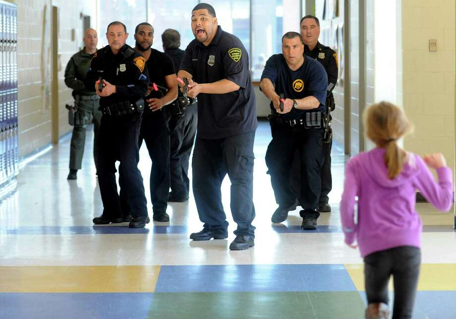 """James Spodnik, a security officer at Fairchild-Wheeler Multi-Magnet High School, is in the point position during """"active shooter"""" training Wednesday, April 16, 2014, at Cesar Batalla School in Bridgeport, Conn. Photo: Autumn Driscoll / Connecticut Post"""