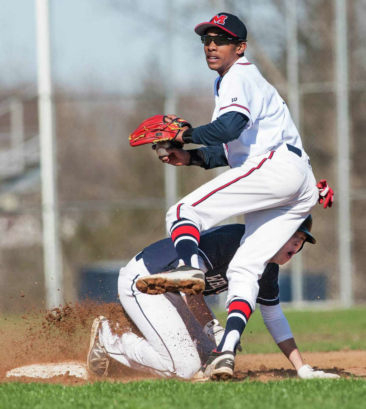Staples high school's Nathan Panzer runs into Brien McMahon high school shortstop Edwin Owolo while sliding into second base during a boy's baseball game played at Brien McMahon high school, Norwalk, CT on Wednesday, April, 16th, 2014.