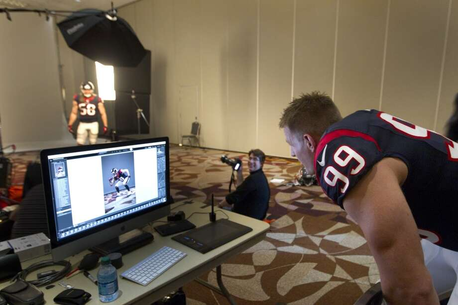 Texans defensive end J.J. Watt takes a look at a photo of linebacker Brooks Reed. Photo: Brett Coomer, Houston Chronicle