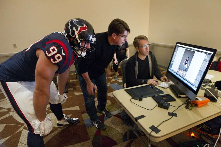 "Texans defensive end J.J. Watt looks at one of the photos taken of him with photographer Robert Seale, center, and his assistant Nathan Lindstrom while shooting the ""We Are Texans"" promotional campaign. Photo: Brett Coomer, Houston Chronicle"