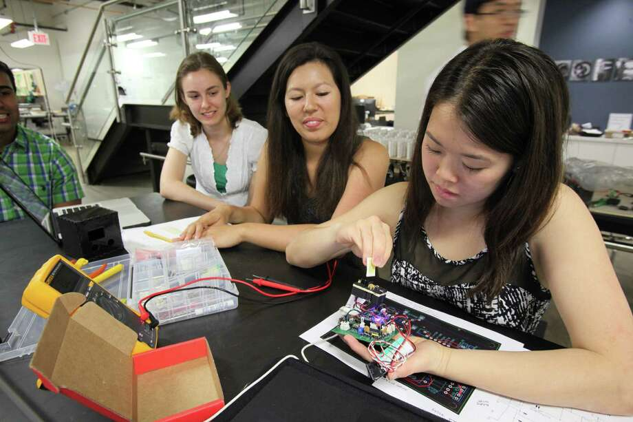 Bio engineer student Melody Tan, 22, holds her project as global health technology student Rohan Shan, 22, Stephanie Tzouanas, 22, and Monica Barrera, 21, view results as Team Biliquant test their project at the Oshman Engineering Design Kitchen at Rice University on April 14, 2014, in Houston, Tx. Photo: Mayra Beltran, Houston Chronicle / © 2014 Houston Chronicle