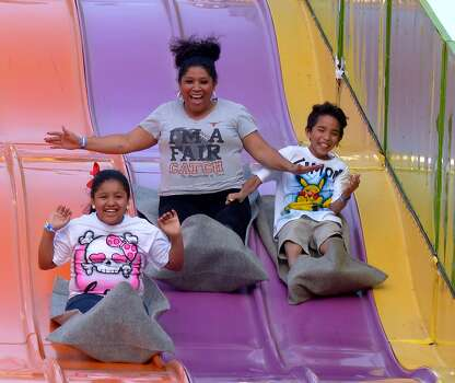 A family enjoys a slide during Fiesta Carnival 2014 in the Alamodome parking lot on April 16, 2014. The carnival runs through April 27. Photo: Billy Calzada, San Antonio Express-News /  San Antonio Express-News