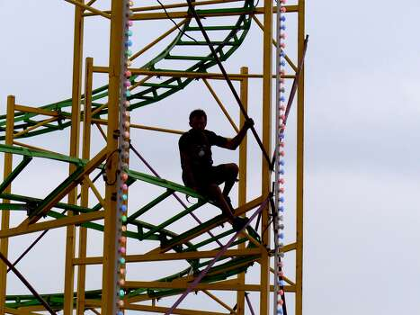 A man works on a roller coaster during Fiesta Carnival 2014 in the Alamodome parking lot on April 16, 2014. The carnival runs through April 27. Photo: Billy Calzada, San Antonio Express-News /  San Antonio Express-News