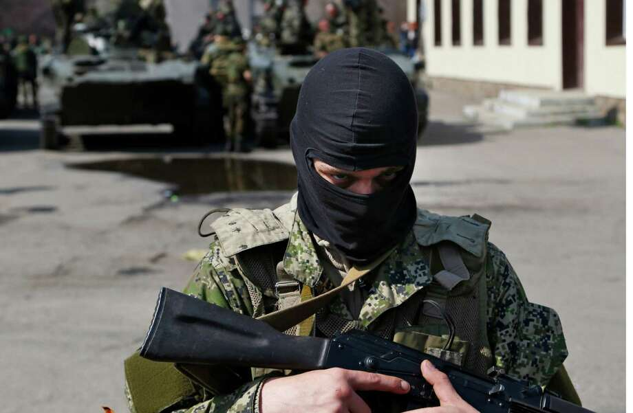 A masked gunman guards combat vehicles with Russian, Donetsk Republic and Ukrainian paratroopers, flags and gunmen on top, parked in downtown of Slovyansk on Wednesday, April 16, 2014. The troops on those vehicles wore green camouflage uniforms, had automatic weapons and grenade launchers and at least one had the St. George ribbon attached to his uniform, which has become a symbol of the pro-Russian insurgency in eastern Ukraine. (AP Photo/ Sergei Grits) Photo: Sergei Grits, AP / AP