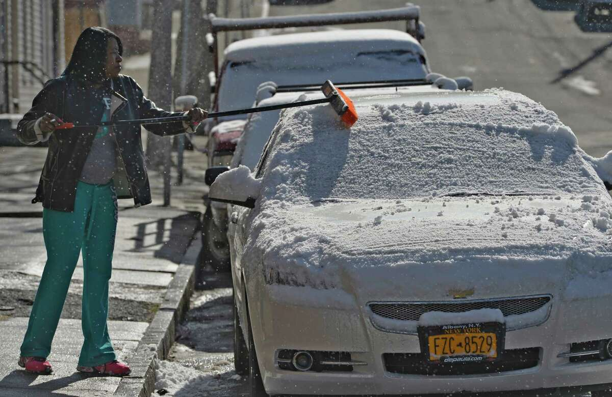Following an overnight snowfall, Noreen Pompey cleans the remaining snow from her care Wednesday morning, April 16, 2014, on Ingalls Avenue in Troy, N.Y. (Skip Dickstein / Times Union)