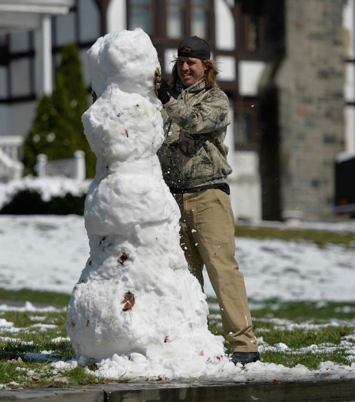 Garrett Gnade took time to make a snowman on Saratoga Avenue Wednesday morning, April 16, 2014, in Waterford, N.Y. A spring snowfall covered the Capital Region. (Skip Dickstein / Times Union)