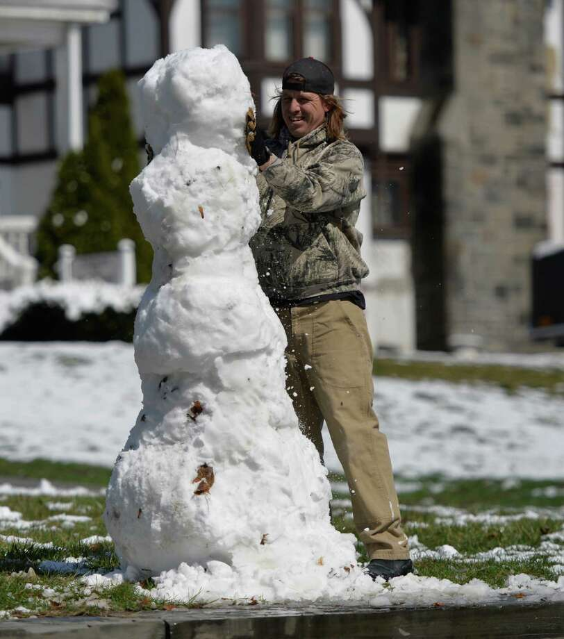 Garrett Gnade took time to make a snowman on Saratoga Avenue Wednesday morning, April 16, 2014, in Waterford, N.Y. A spring snowfall covered the Capital Region. (Skip Dickstein / Times Union) Photo: Skip Dickstein