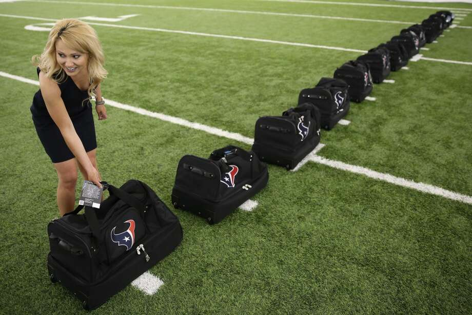 Former Houston Texans cheerleader Amanda Golden from 2007-11 puts out Cheerleading bags before the announcement. Fifty girls showed up on April 16, 2014 at the Houston Texans practice facility in Houston, Texas to see which 35 girls made the 2014-2015, Houston Texans Cheerleading Team. Photo: Thomas B. Shea