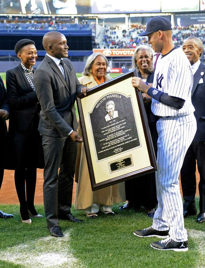 New York Yankees' Derek Jeter, right, presents a photo of a Nelson Madela plaque to, from left, Lindo Mandela, Zondwa Mandela, Rachel Robinson and Sharon Robinson before Game 2 of an interleague baseball doubleheader against the Chicago Cubs, Wednesday, April 16, 2014, at Yankee Stadium in New York. Lindo is the wife of Zondwa, Zondwa is the grandson of Nelson, Rachel is the widow of baseball great Jackie Robinson and Sharon is the daughter of Rachel and Jackie. (AP Photo/Bill Kostroun) ORG XMIT: NYY212 Photo: Bill Kostroun / FR51951 AP