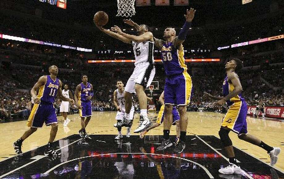 San Antonio Spurs' Cory Joseph goes for two as Los Angeles Lakers' Robert Sacre defends during the second half at the AT&T Center, Wednesday, April 16, 2014. The Lakers won 113-100. Photo: Jerry Lara/Express-News