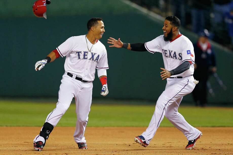 Leonys Martin (left), who had the game-winning hit for the Rangers, celebrates with Elvis Andrus. Photo: Tom Pennington / Getty Images / 2014 Getty Images