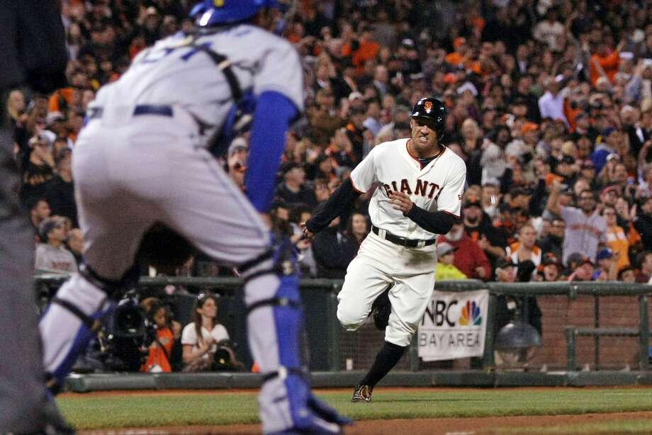 Hunter Pence heads home as catcher Drew Butera awaits a throw on Buster Posey's single to left field in the third inning. Photo: Lance Iversen, Reuters