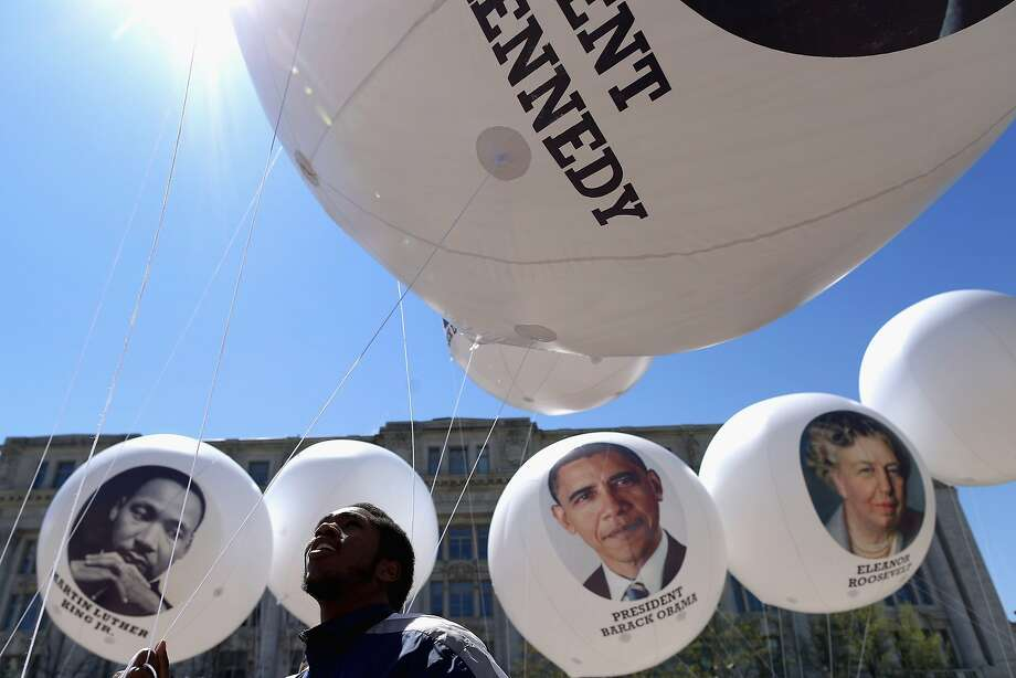WASHINGTON, DC - APRIL 16:  Bay Peters, 20, of the District of Columbia attempts to control large balloons filled with helium in high winds during the Emancipation Day parade April 16, 2014 in Washington, DC. A public holiday in nation's capital, April 16, 1862, is the date President Abraham Lincoln signed the Compensated Emancipation Act for the release of certain persons held to service or labor in the District of Columbia. The Act freed about 3,100 enslaved persons in DC nine months before Lincoln issued his famous Emancipation Proclamation.  (Photo by Chip Somodevilla/Getty Images) Photo: Chip Somodevilla, Getty Images