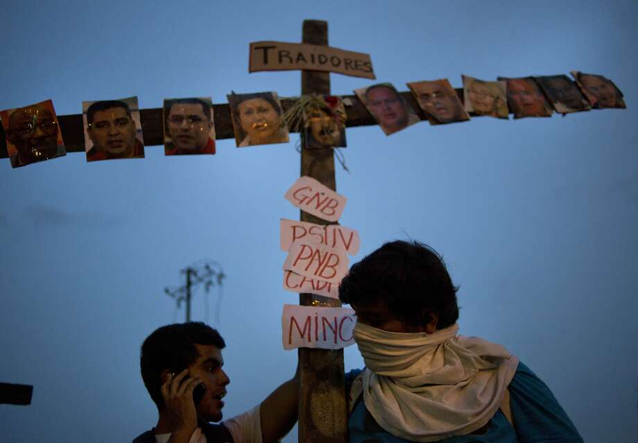 "Anti-government protesters carry a cross covered with photos of government officials and supporters under the Spanish word ""Traitors"" at a demonstration during Holy Week in Caracas, Venezuela, Wednesday, April 16, 2014. The opposition wants President Nicolas Maduro's government to free jailed opponents and create an independent truth commission to determine responsibility for deaths tied to protests that have rocked the nation since February. (AP Photo/Ramon Espinosa) Photo: Ramon Espinosa, Associated Press"