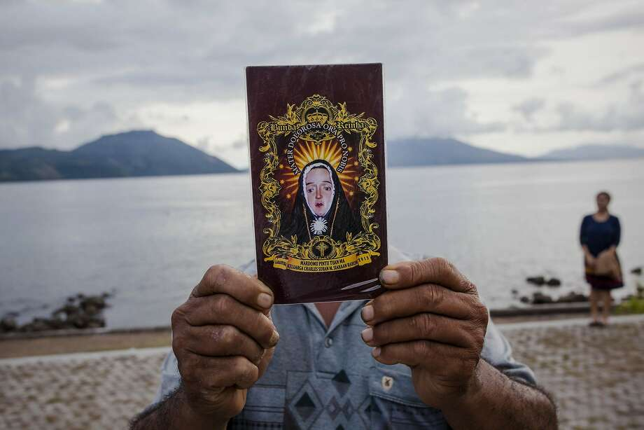 LARANTUKA, EAST NUSA TENGGARA, INDONESIA - APRIL 16: A catholic worshipper holds Virgin Mary picture as he prepare for Holy Week celebrations, known as 'Semana Santa' on April 16, 2014 in Larantuka, East Nusa Tenggara, Indonesia. Easter celebrations in Larantuka started in the 16th century, when Portuguese missionaries entered and acculturated the local people. The ritual appeals to the pilgrims and people from various regions in Indonesia, who come to follow the procession. Holy Week marks the last week of Lent and the beginning of Easter celebrations. Catholics make up approximately 3% per cent of the population of the predominantly Muslim country. (Photo by Ulet Ifansasti/Getty Images) *** BESTPIX *** Photo: Ulet Ifansasti, Getty Images