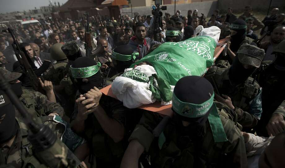 Mourners carry the body one of three of Hamas militants who were killed in an explosion, during their funeral in the al-Nusairat refugee camp, in central Gaza Strip, on April 16, 2014. Witnesses said the blast took place at a training camp belonging to Hamas's armed wing the Ezzedine al-Qassam Brigades east of the city of Khan Yunis in the southern Gaza Strip, but it was unclear what caused the explosion. AFP PHOTO/MAHMUD HAMSMAHMUD HAMS/AFP/Getty Images Photo: Mahmud Hams, AFP/Getty Images