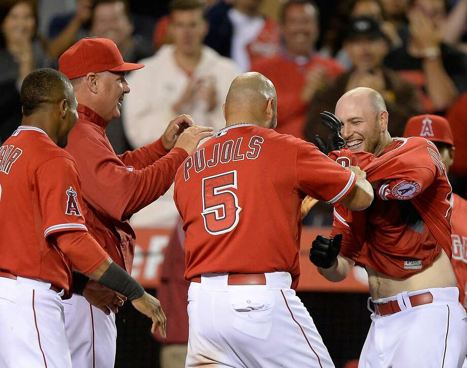 Albert Pujols gives Chris Iannetta a jersey-roughing welcome as Iannetta reaches the plate on his game-ending homer. Photo: Harry How, Getty Images