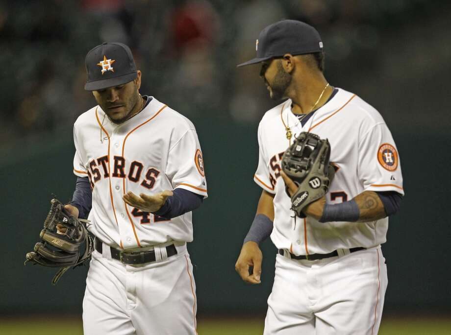 Astros second baseman Jose Altuve, left, with shortstop Jonathan Villar, right, takes a look at his hand after catching a line drive hit by Lorenzo Cain. Photo: Melissa Phillip, Houston Chronicle
