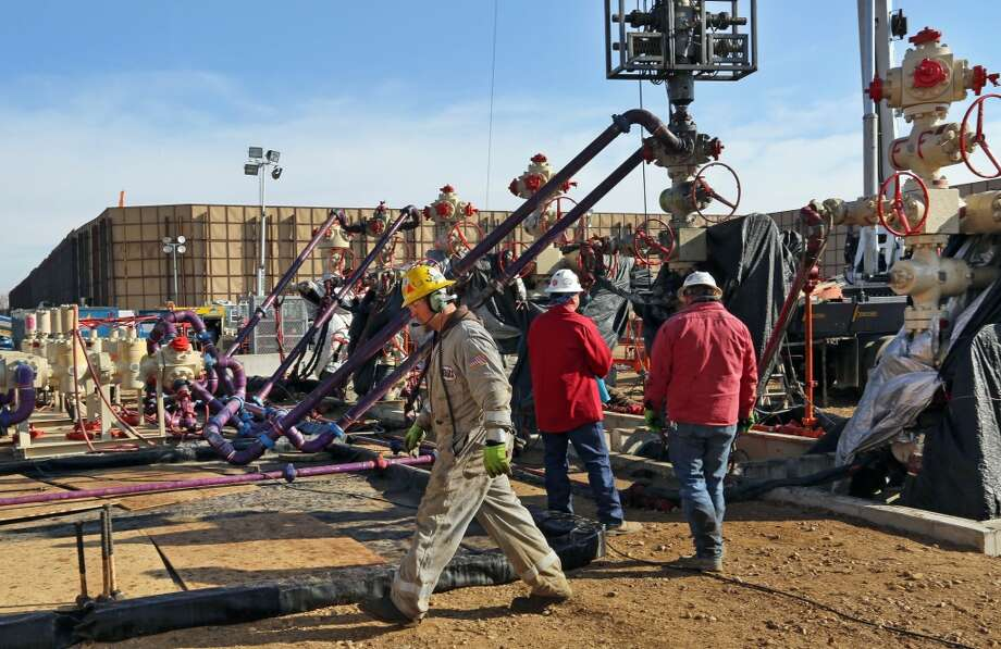 Mike Hamilton, ground and crew supervisor for Bayou Well Services, walks past the well heads during a hydraulic fracturing operation at an Encana Corp. well pad near Mead, Colo. It takes a few weeks for the half dozen wells on a typical pad to be fracked, after which the petroleum products are extracted for years by operators like Encana. Photo: Brennan Linsley, AP
